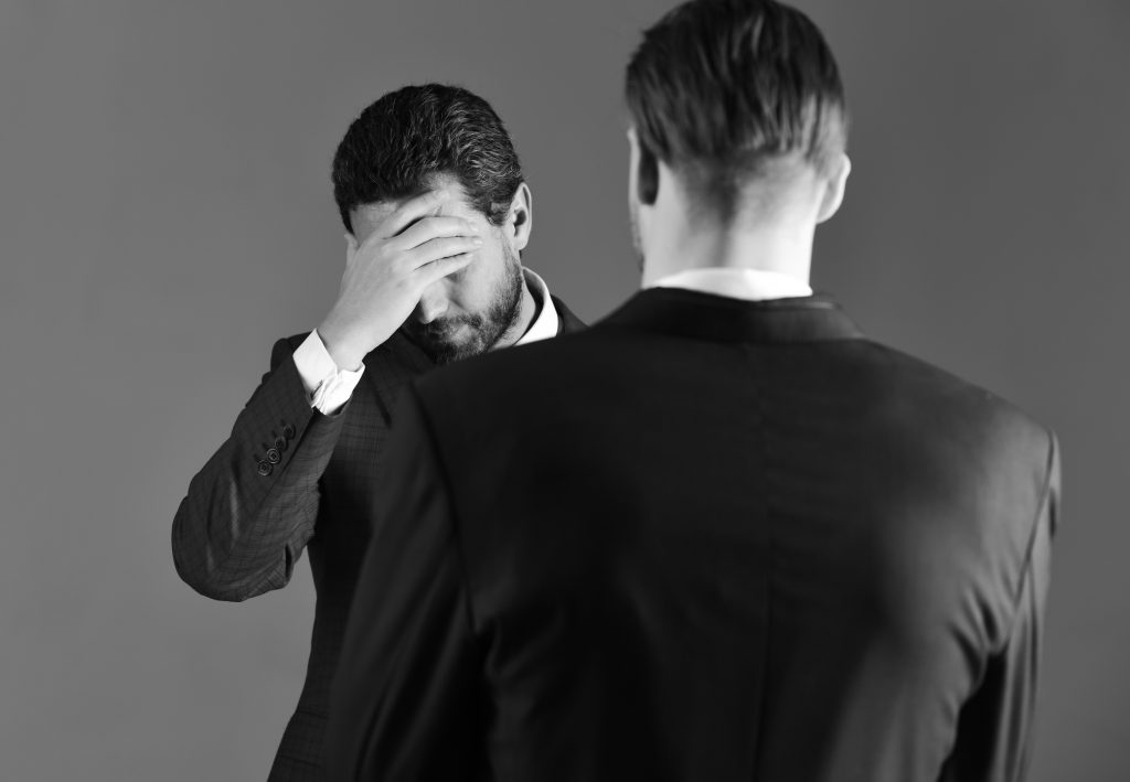 Difficulties in business relations. Business negotiations concept. Man in jacket listening his business partner with desperate expression. Boss and employee speaking at meeting on dark background.