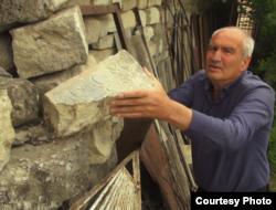 Наріман Ібадлаєв показує фрагмент надгробку. Бахчисарай